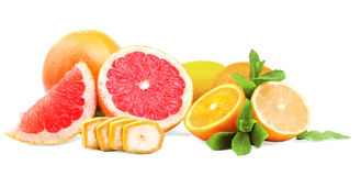 Various citruses  on a white background. Juicy oranges, lemons and grapefruits. A sliced banana and peppermint leaves. A group of fresh bright fruits and mint Stock Image