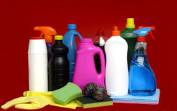 Various cleaning products of different colors. Various cleaning products with different colors and red background stock photo
