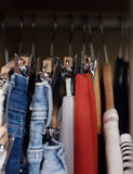 Various clothes hanged in wardrobe. Clothes hang in the closet. Jeans and skirts on chrome plated clothespins. Tightly hanging clothes in the wardrobe royalty free stock image