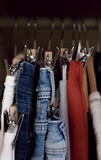 Various clothes hanged in wardrobe. Clothes hang in the closet. Jeans and skirts on chrome plated clothespins. Tightly hanging clothes in the wardrobe royalty free stock photos