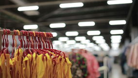 Various clothes on hangers in a store. slider shot. A large clothing store. Various clothes hanging on hangers in a store. slider shot stock footage
