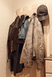 Various clothes hanging on coat rack. Royalty Free Stock Photos