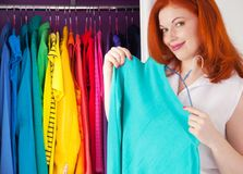 The red-haired woman chooses her clothes near the cupboard. Clot stock photography