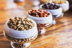 Various coffee beans on wooden background. Royalty Free Stock Image