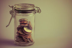 Various coins in closed jar retro vintage photo. Stock Photos