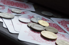 Various coins and playing cards Royalty Free Stock Photo