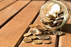 Various coins are scattered on a wooden table. The concept of poverty stock images