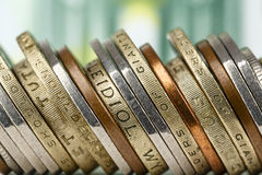 Various coins shown against banknote background Stock Images