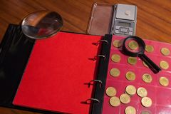 Numismatic materials and album for coins - numismatic scene. Various coins on a wooden table with magnifying glass Stock Photography