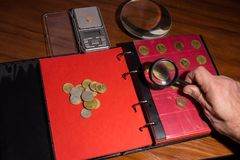 Collectors Folder for Coin or money collecting in ring folder or binder. Various coins on a wooden table with magnifying glass, numismatic materials and an album Royalty Free Stock Photography