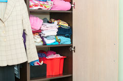 Various color clothes are organized at shelves in wardrobe. Various color clothes are organized at shelves in open wardrobe Stock Images
