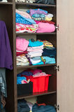 Various color clothes at shelves in wardrobe. Various color clothes are in shelves in wardrobe Stock Photos