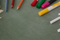Various color pencils, marker pens and chalk on chalkboard Royalty Free Stock Photo