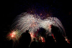 Various colored fireworks with silhouette of people. Royalty Free Stock Images
