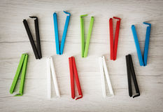 Various colorful bag clips on the wooden background Royalty Free Stock Photo