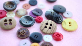 Various colorful buttons on pink rotating table stock video footage