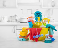 Various colorful cleaning products on table over blurred kitchen background Royalty Free Stock Photo