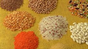 Various colorful dried legumes. On a yellow background stock video