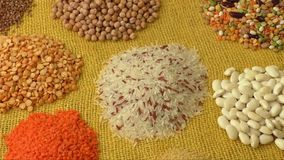 Various colorful dried legumes on a yellow background stock video footage