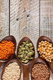 Various colorful grains and seeds in wooden spoons - close up stock image