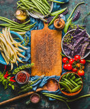 Various colorful pea and beans  pods around empty cutting board with cooking ingredients and wooden spoon, top view Royalty Free Stock Photo