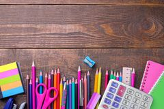 Various colorful school and office supplies on a brown wooden table. royalty free stock photos