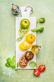 Various colorful sliced tomatoes on white marble cutting board Stock Images