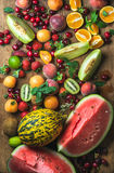 Various colorful tropical fruit selection on rustiv wooden background. Top view. Watermelon, melon, strawberries, cherries, kiwi, peaches, apricots, oranges Royalty Free Stock Images