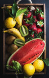 Various colorful tropical fruit selection in wooden tray over dark background Stock Photos
