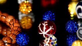 Various colors of beads isolated on black. Colorful, brilliant, various beads isolated on black background, cam moves to the left, close up stock video footage