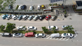 Various colors, make and shapes of cars parked in various position in rows of cars in line parked stock image
