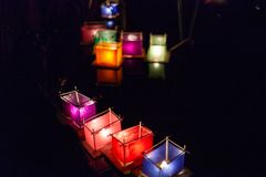Various colors of silk lantern boats with lit candles inside stock image