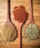 Top view of some spices on wood spoons. Various colors spices on wood spoons over a wooden surface. Directly above view Stock Photo