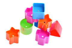 Various coloured blocks for shape sorter toy. Red, blue, green, orange and magenta blocks used for play with shape sorter toy isolated on seamless white Stock Images
