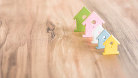 Various Coloured House Symbols staying in one Line on brown wooden Surface Royalty Free Stock Photo