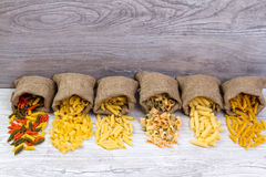 Various combinations of pasta on wooden background, burlap bags, bamboo bowls. diet and nutritional concept. Royalty Free Stock Image
