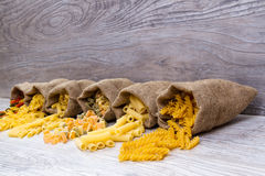 Various combinations of pasta on wooden background, burlap bags, bamboo bowls. diet and nutritional concept. Royalty Free Stock Images