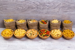 Various combinations of pasta on wooden background, burlap bags, bamboo bowls. diet and nutritional concept. Stock Image