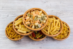 Various combinations of pasta on wooden background, burlap bags, bamboo bowls. diet and nutritional concept. Royalty Free Stock Photos