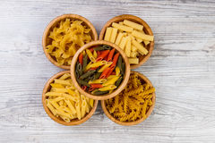 Various combinations of pasta on wooden background, burlap bags, bamboo bowls. diet and nutritional concept. Royalty Free Stock Photo