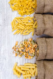 Various combinations of pasta on wooden background, burlap bags, bamboo bowls. diet and nutritional concept. Royalty Free Stock Photography