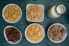 Various conrflake cereals in bowls and milk Royalty Free Stock Photography