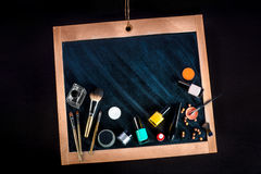 Various cosmetic and makeup on chalkboard Stock Photo