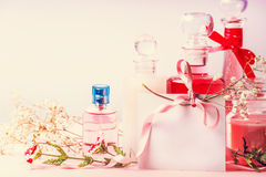 Various cosmetic products bottles and jars with flowers and  empty paper card with ribbon for Invitation, coupon, discount and sal Royalty Free Stock Photo