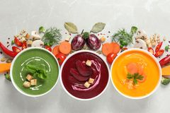 Various cream soups and ingredients on grey background. Flat lay. Healthy food royalty free stock photo