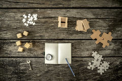 Various cubes, pegs, puzzles and a key lying on wooden desk arou Stock Photography