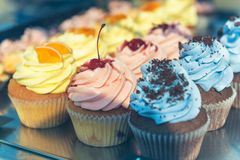 Various cupcakes on a street food festival. Retro stylized shot, selective focus Royalty Free Stock Photography