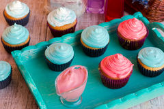 Various cupcakes on a wooden tray of mint color. Cupcakes with raspberry and mint cream Royalty Free Stock Photo