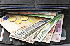 Various currencies in purse Royalty Free Stock Photo