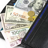 Various currencies in purse Stock Images